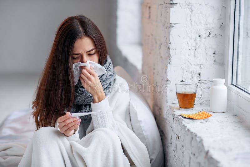 La femme malade a attrapé la maladie froide et se sentante et l'éternuement dans le chiffon de papier Plan rapproché de la belle  photos libres de droits