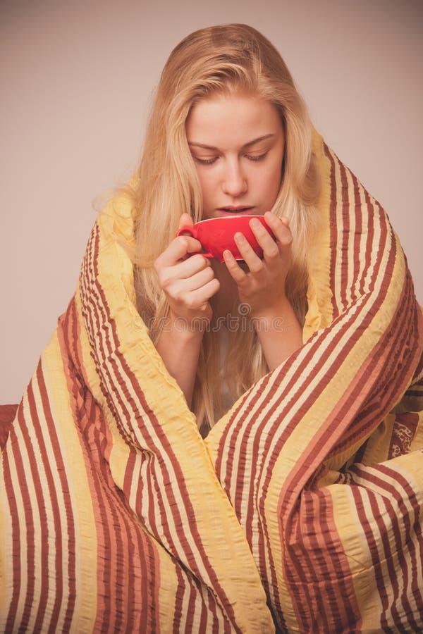 La femme malade s'asseyant sur le mauvais enveloppé dans une défectuosité couvrante de sentiment, a images libres de droits