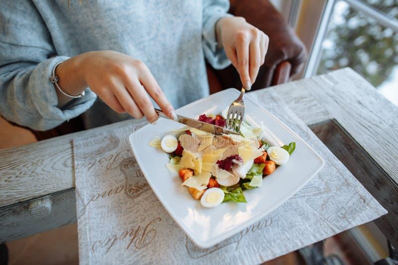 La femme mange d'une salade de César délicieuse photo stock