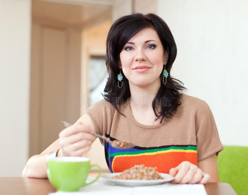 La femme mange de la céréale de sarrasin photographie stock libre de droits