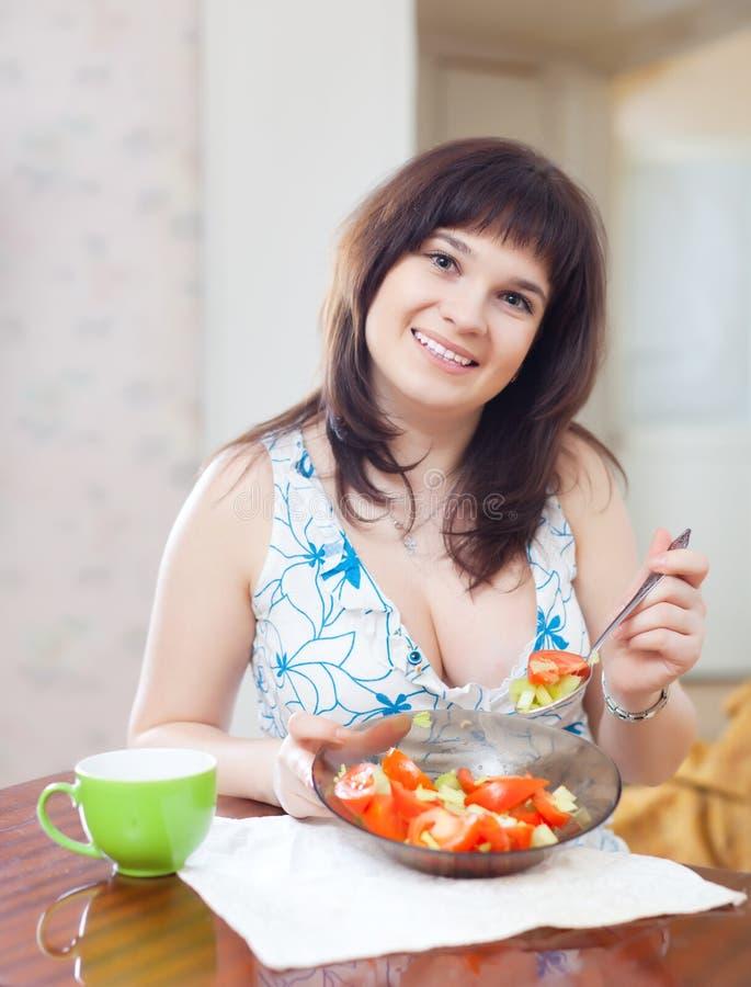 La femme mange de la salade de veggie sur le sofa à l'intérieur photographie stock libre de droits