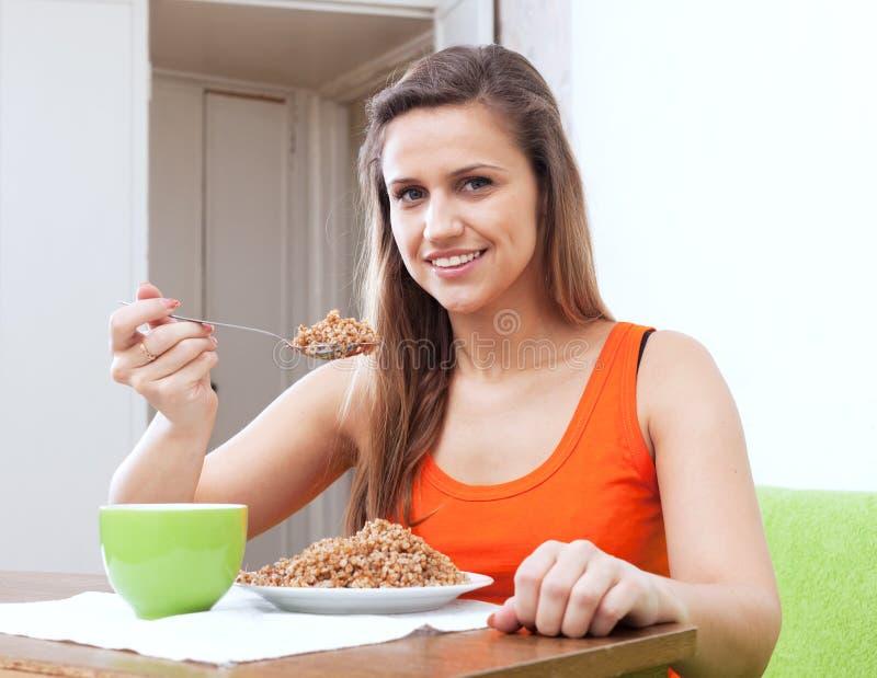 La femme mange du gruau de sarrasin avec la cuillère images stock