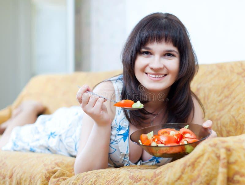 La femme mange l'intérieur de salade à la maison photos stock