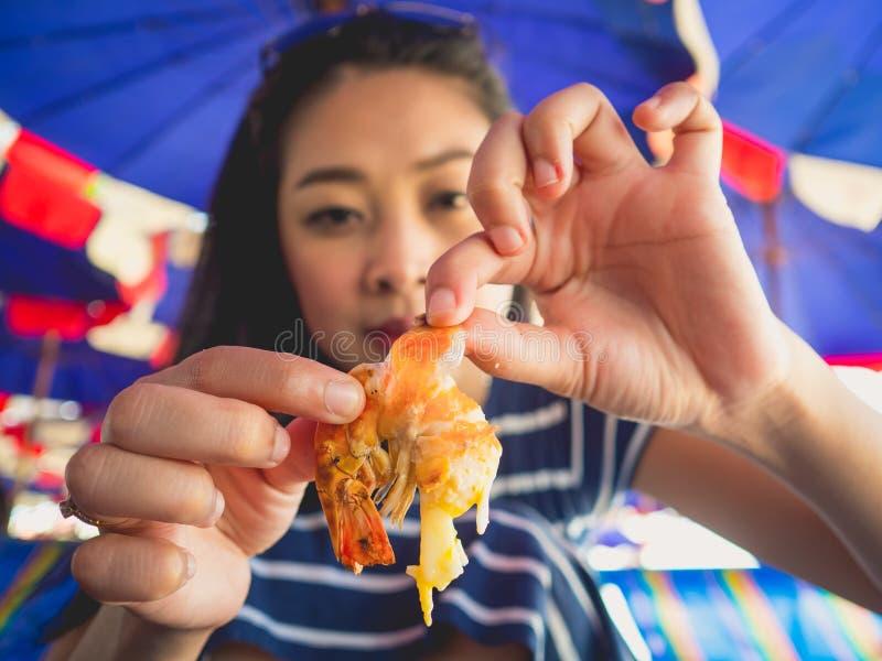 La femme mangeant des gens du pays a grillé des fruits de mer de plage de la Thaïlande images libres de droits