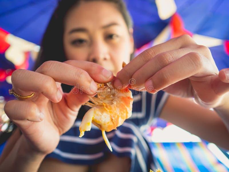 La femme mangeant des gens du pays a grillé des fruits de mer de plage de la Thaïlande photo libre de droits
