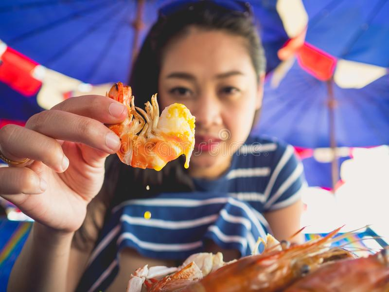 La femme mangeant des gens du pays a grillé des fruits de mer de plage de la Thaïlande images stock