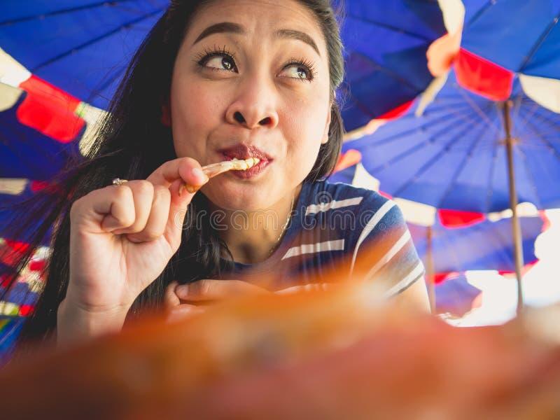 La femme mangeant des gens du pays a grillé des fruits de mer de plage de la Thaïlande photographie stock