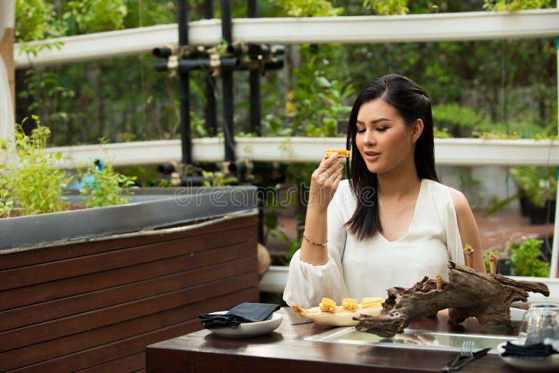 La femme mangent l'herbe d'épice de nourriture d'Idia de fusion avec du maïs photographie stock