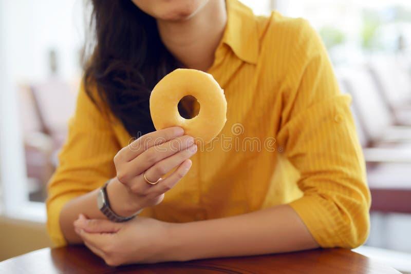 La femme mangent le beignet photographie stock libre de droits