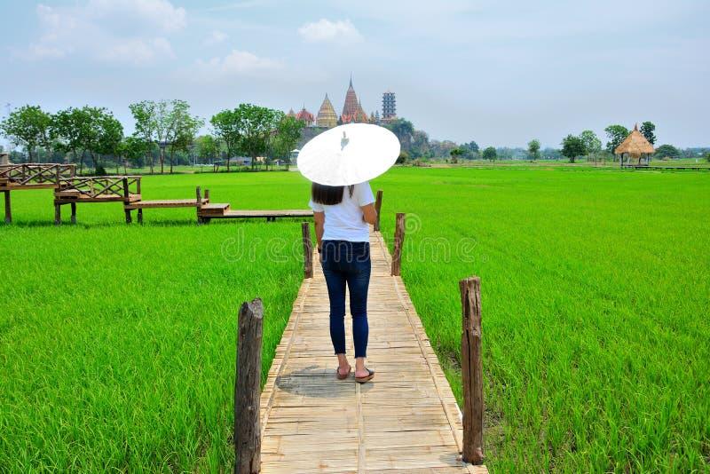 La femme a marché de retour et a tourné un parapluie blanc sur le pont en bois Il y a les prairies et le fond de temples bouddh photos libres de droits