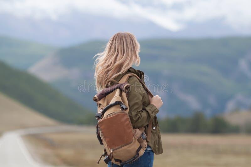 La femme marche sur une route goudronnée avec un sac à dos sur elle de retour photo libre de droits