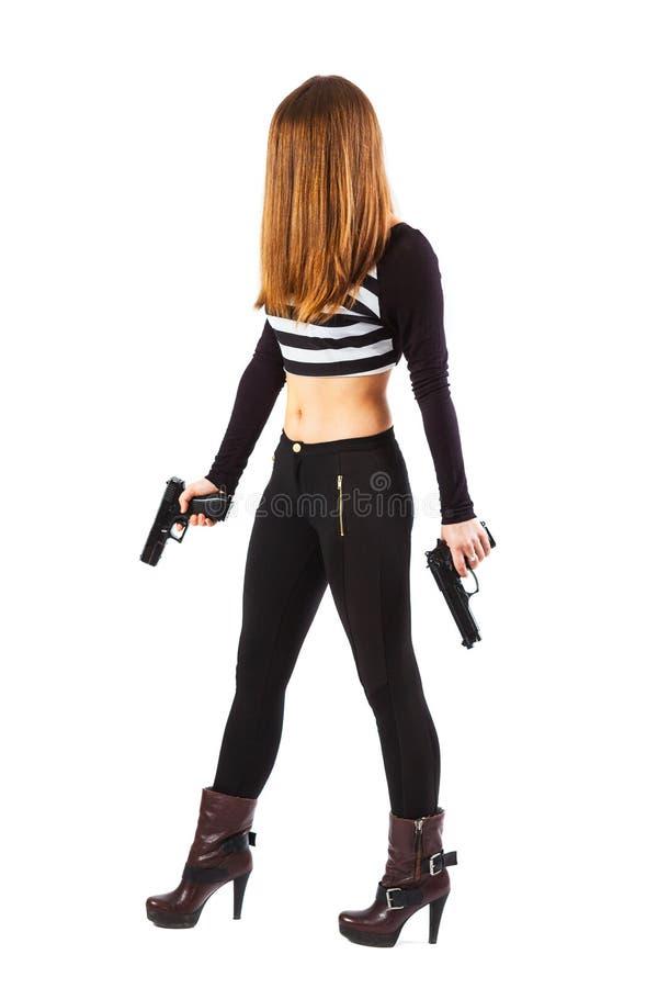 La femme menaçante et sexy avec des armes à feu marche photos stock