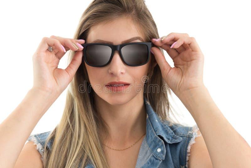 La femme met dessus les lunettes de soleil Gilet de port de jeans de personne blonde photo libre de droits
