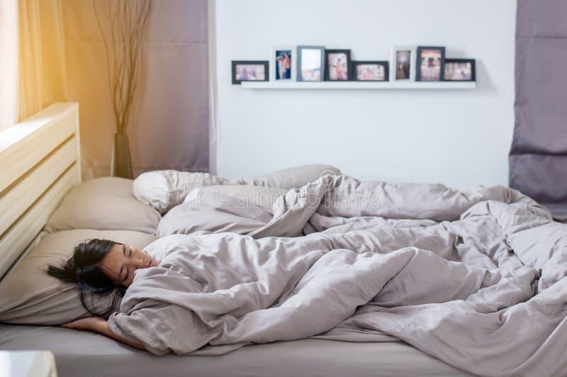 La femme mettant la couverture avec ont une fièvre sur le lit pendant le matin photo stock