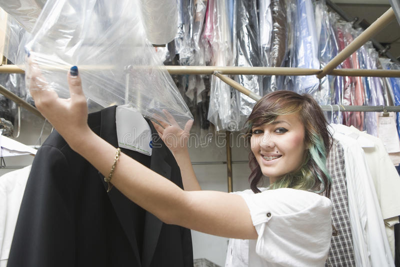 La femme mettant le plastique pour sécher a nettoyé le manteau dans la blanchisserie photographie stock