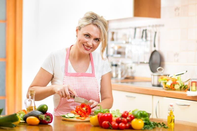 La femme mignonne coupe le paprika pour la salade à la table de cuisine photo stock