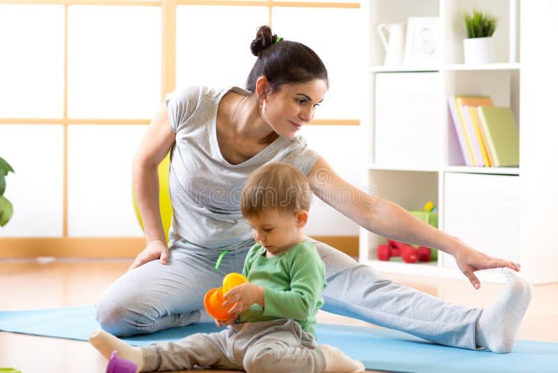 La femme mignonne folâtre est engagée dans la forme physique et le yoga à la maison Son enfant de fils par la séance et jouer pro image stock