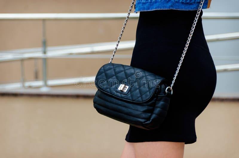 La femme mince dans une robe noire tient un petit sac en cuir noir photos stock