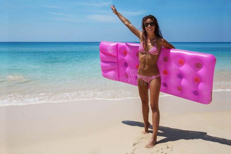 La femme mince de brune les prennent un bain de soleil avec un matelas d'air image libre de droits
