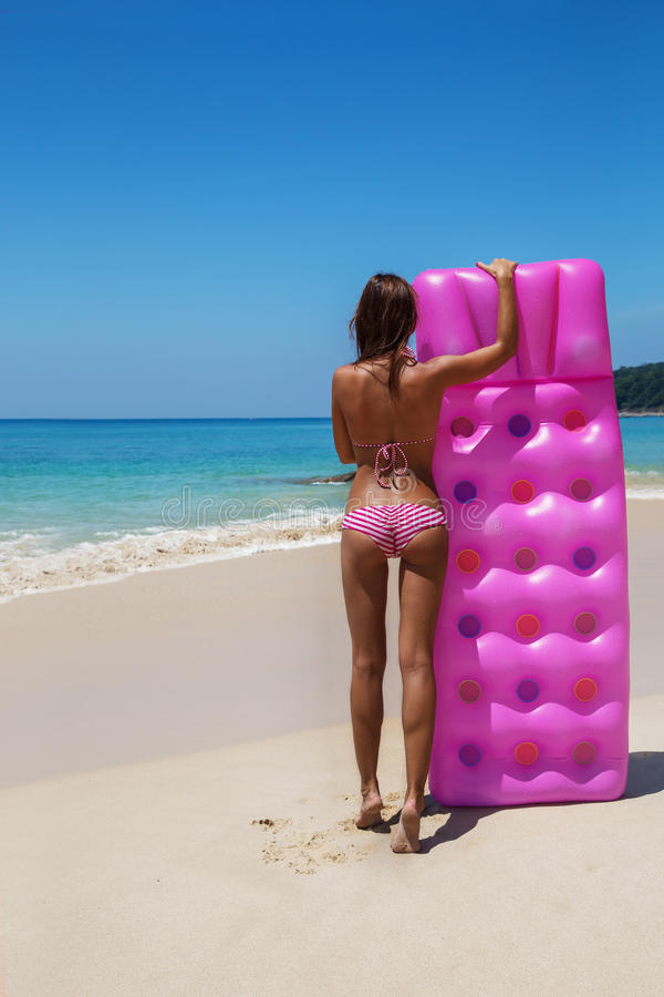 La femme mince de brune les prennent un bain de soleil avec un matelas d'air images stock