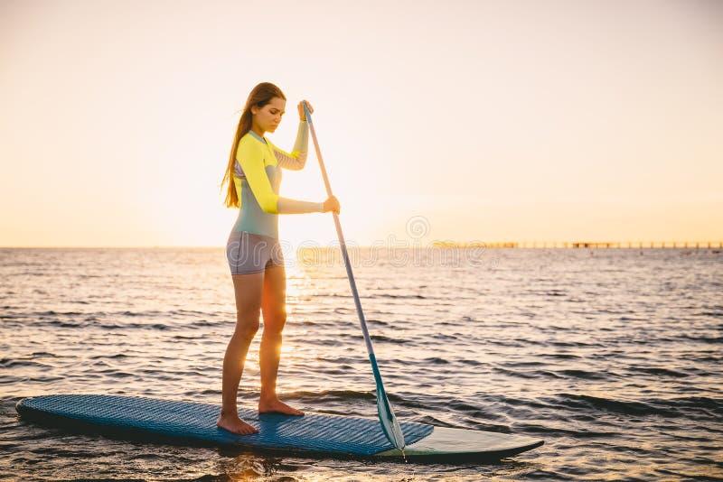 La femme mince parfaite tiennent la palette surfant dans l'océan avec de belles couleurs de coucher du soleil images libres de droits