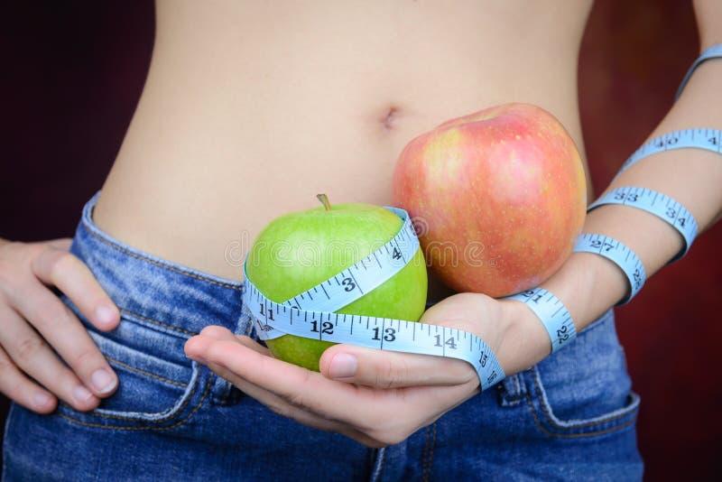 La femme mince porte la pomme verte, mesurant la bande image libre de droits