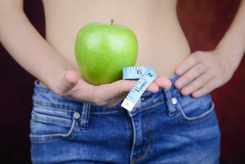 La femme mince porte la pomme verte, mesurant la bande photo stock