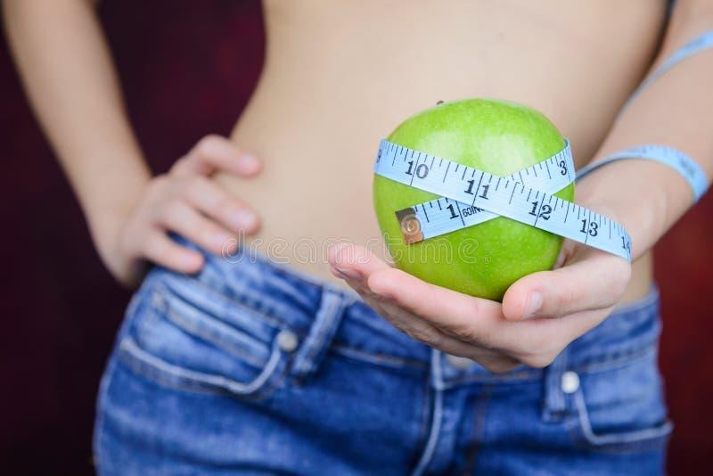 La femme mince porte la pomme verte, mesurant la bande photographie stock