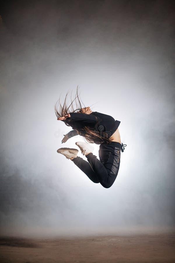 La femme mince saute avec les jambes de recourbement l'adolescent tire des pieds sous elle images libres de droits