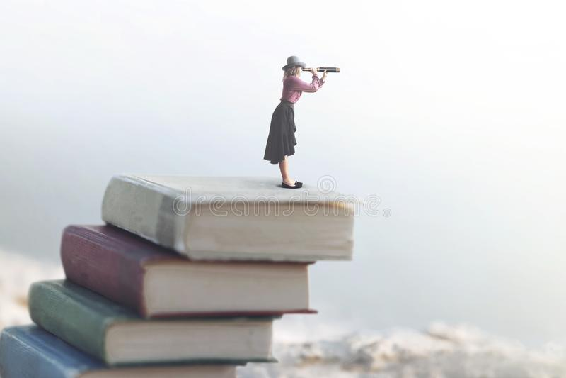 La femme miniature regarde l'infini avec le regard sur une échelle des livres image libre de droits