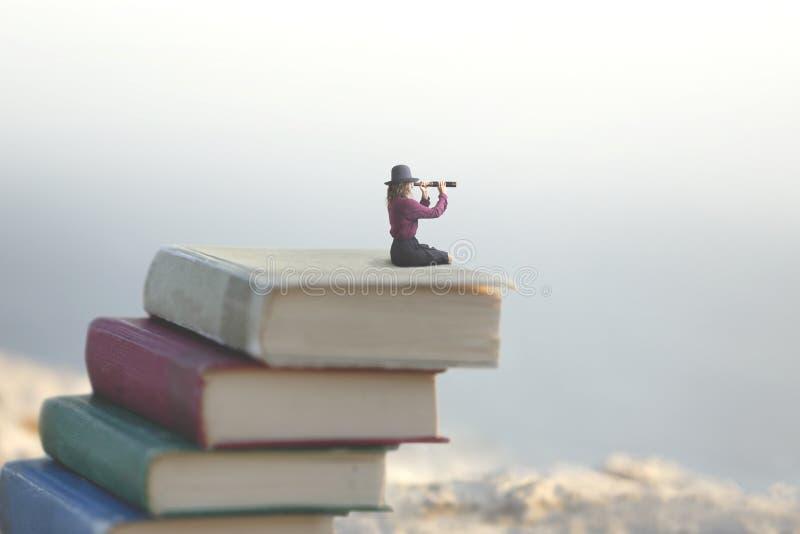 La femme miniature regarde l'infini avec le regard sur une échelle des livres photos stock