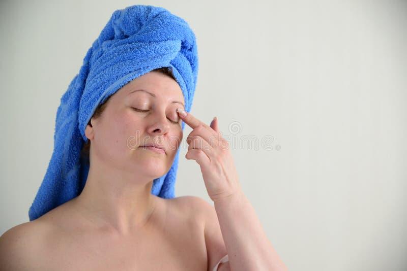 La femme a mis la crème sur la peau de paupière après une douche images libres de droits