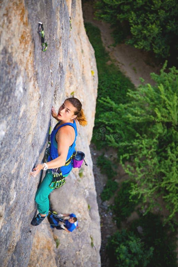 La femme monte la roche image libre de droits