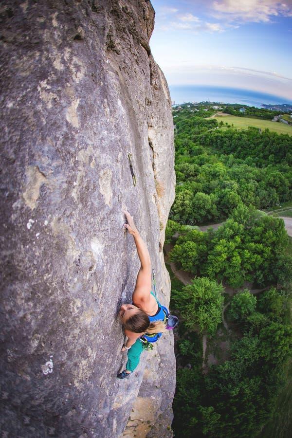La femme monte la roche image stock