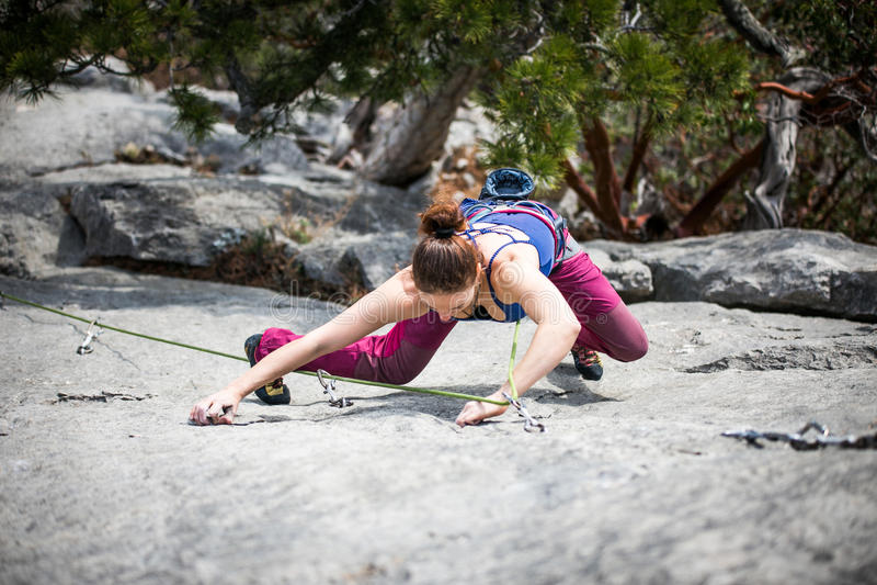 La femme monte une roche photo stock