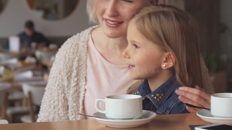 La femme montre à sa fille quelque chose au café image stock