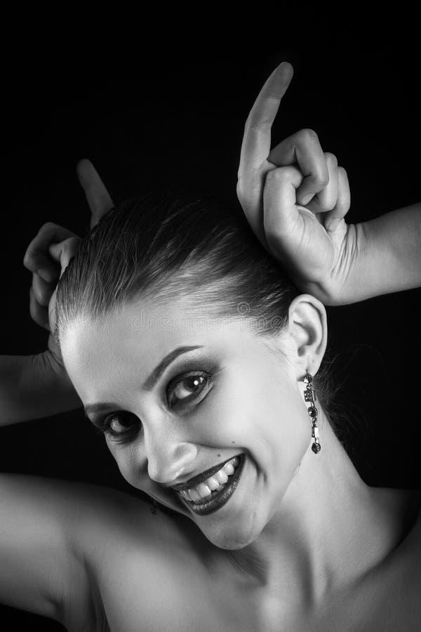 La femme montre des klaxons photo stock