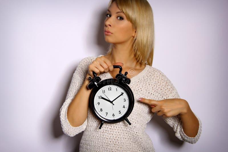 La femme montre le temps photographie stock