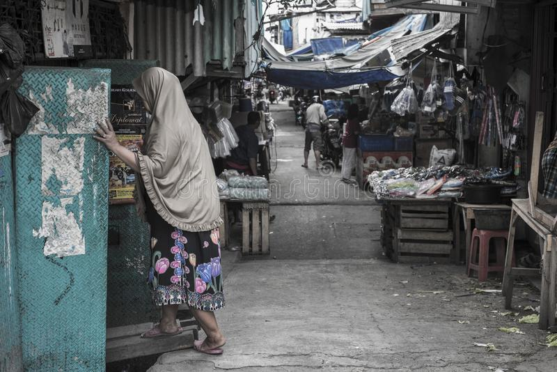 La femme musulmane indonésienne portant le voile marche un sordide à Jakarta, Indonésie photographie stock