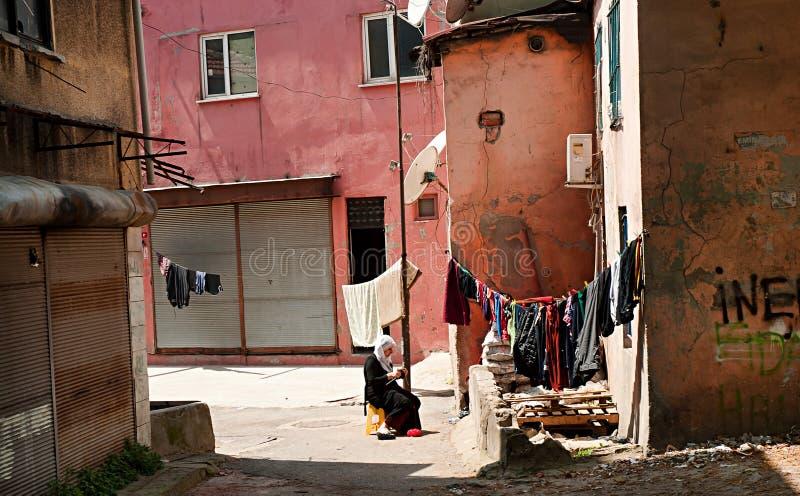La femme musulmane s'assied en dehors de sa maison et tricote des vêtements dans un quartier défavorisé d'Istanbul, Turquie photos stock