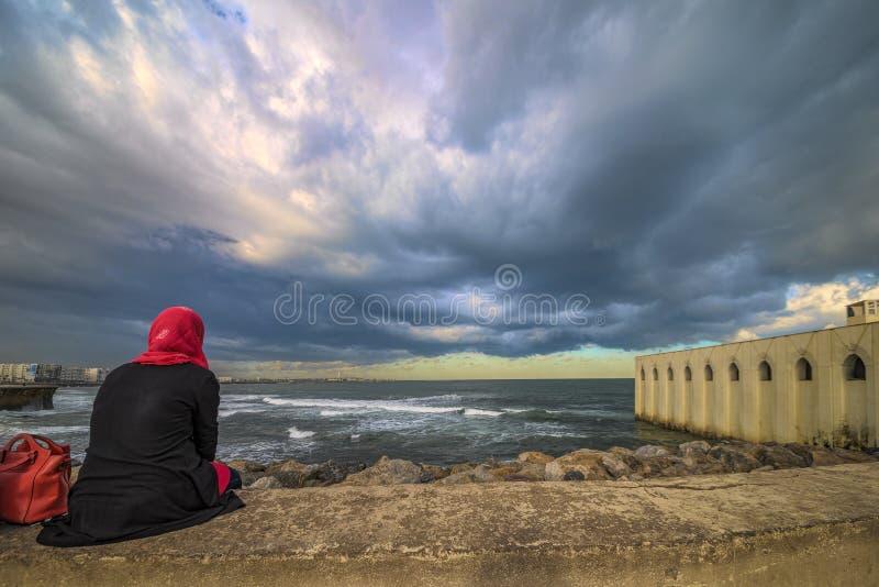 La femme musulmane seule de Casablanca 08-11-2016 A s'assied au bord de la mer sur un mur en pierre regardant fixement l'air mena photographie stock libre de droits