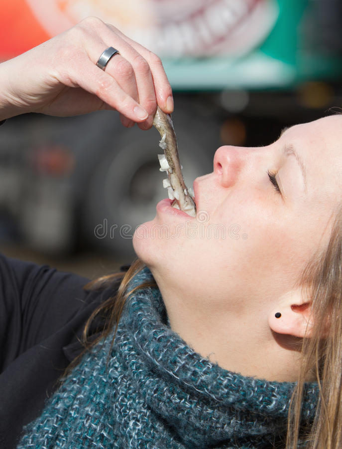 La femme néerlandaise mange les harengs crus typiques images libres de droits