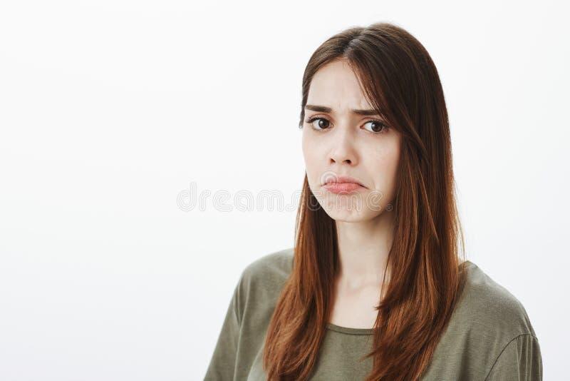 La femme n'a pas aimé comment elle est traitée Portrait de jolie amie contrariée sombre dans le T-shirt vert-foncé, fronçant les  photographie stock