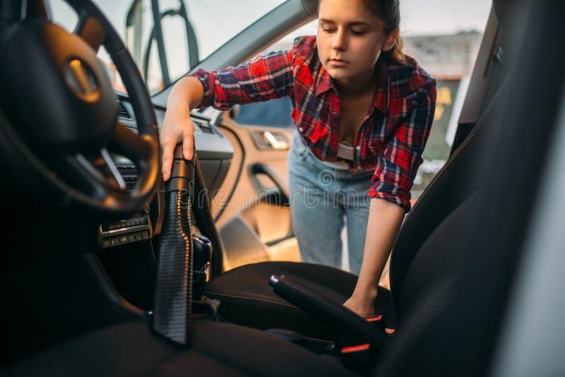 La femme nettoie l'intérieur de voiture avec l'aspirateur photos stock