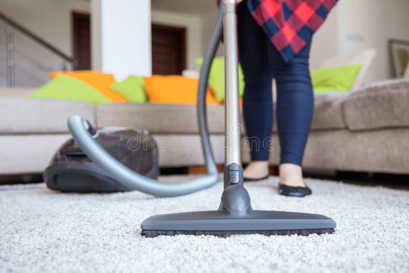 La femme nettoie le tapis gris-clair avec le vide images stock