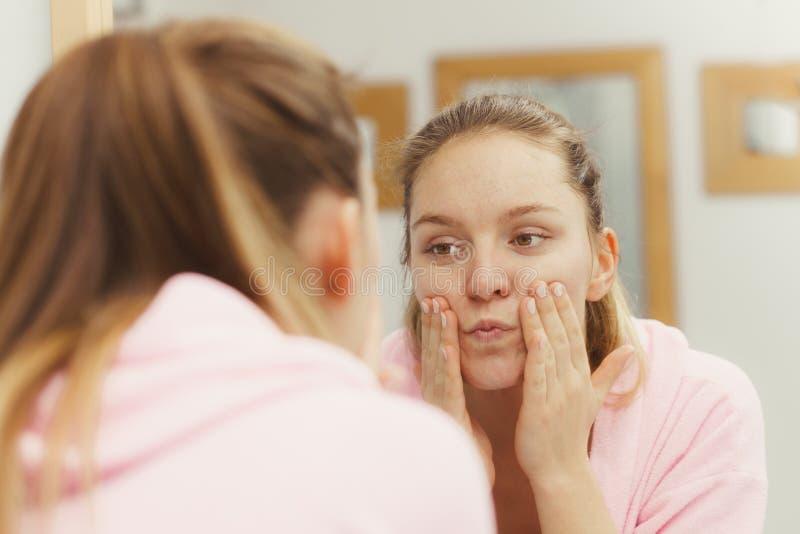 La femme nettoyant son visage avec frottent dans la salle de bains image libre de droits