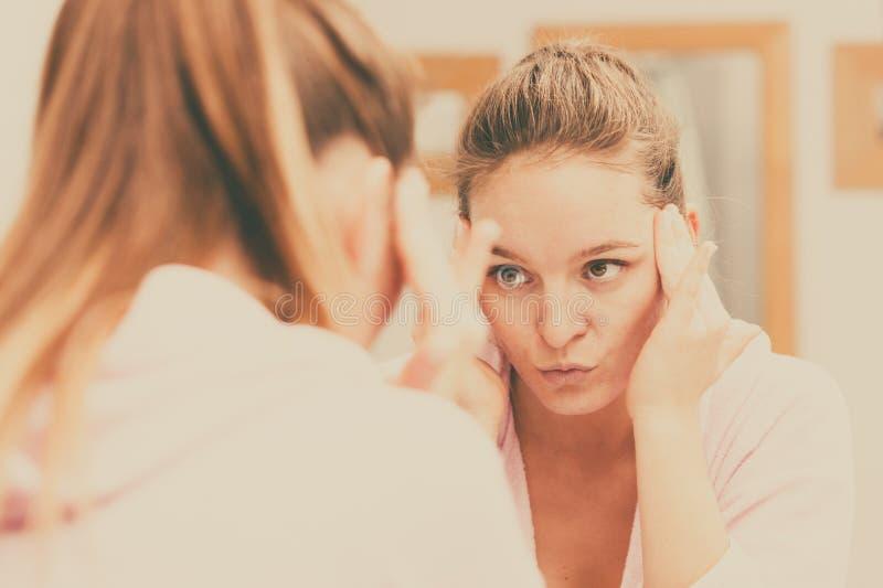 La femme nettoyant son visage avec frottent dans la salle de bains photo stock