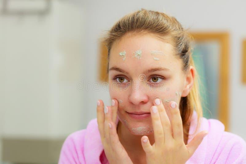 La femme nettoyant son visage avec frottent dans la salle de bains image stock