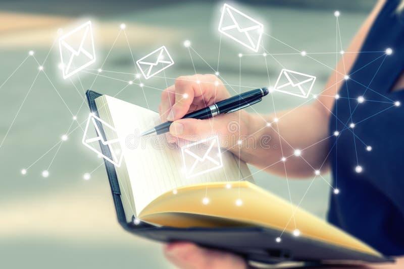 La femme notent des lettres dans le carnet pour envoient le message sans Co image stock