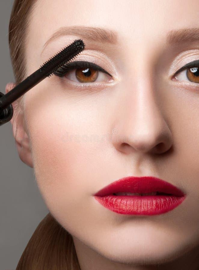 La femme observe avec le beau maquillage et les longs cils Brosse de mascara images stock
